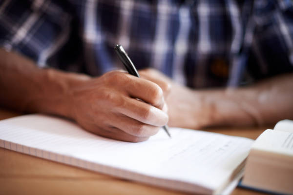 Closeup shot of a young student writing on a note pad