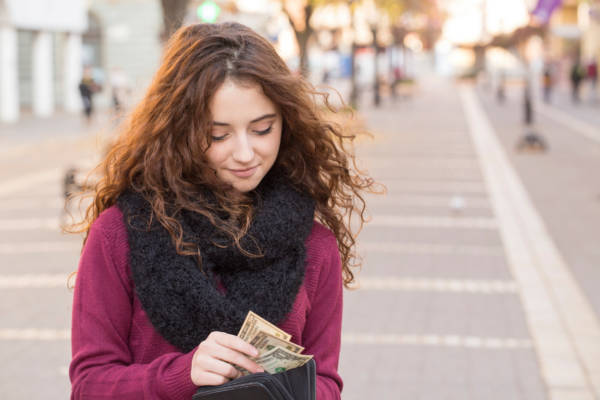 young shopper woman taking out money from wallet on street