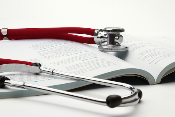 book and stethoscope isolated on white background