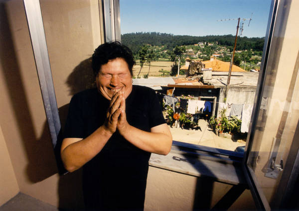 Rosa Coelho praises God that she no longer has to live in the shack visible through the window behind her in Cunha, Portugal. (2001)