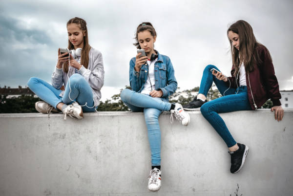 three teenage girls sitting outdoors on concrete wall and looking at their smartphones